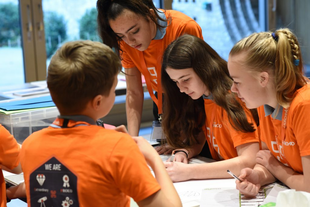 Children working in group orange t-shirts