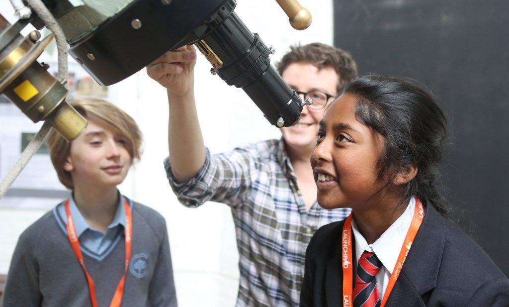 School children looking through telescope