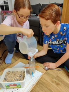Children making bird feeder with plastic bottle