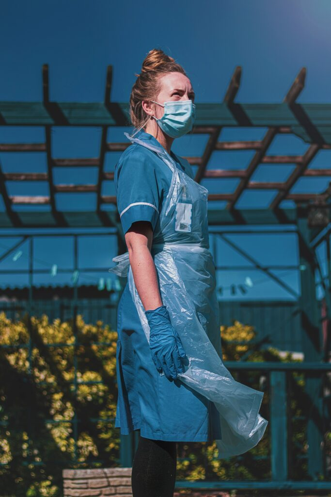Woman standing outside with medical uniform and PPE